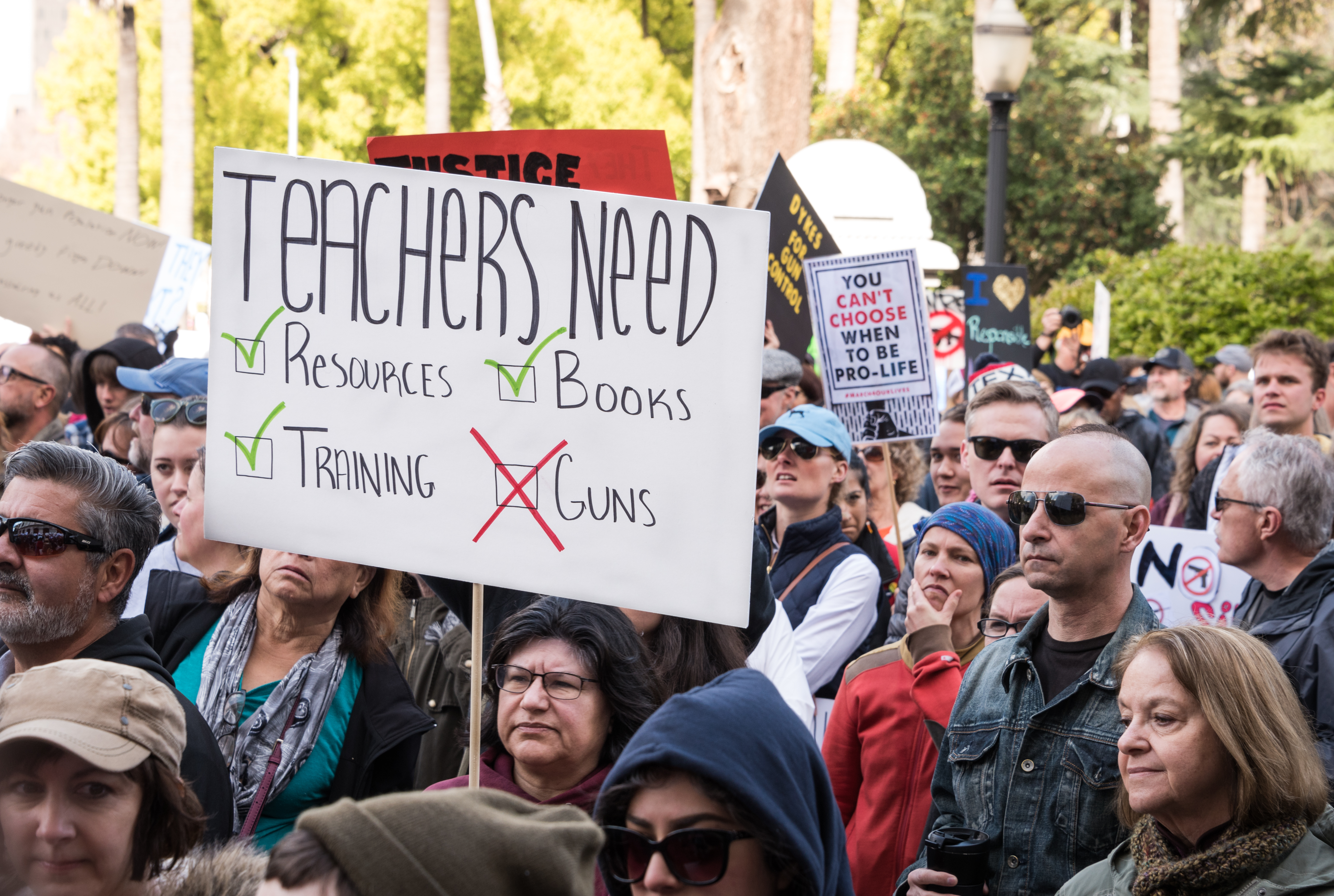 A woman holds a sign advocating for equipping teachers with resources at a March For Our Lives sister rally in Sacramento. Chris Allan / Shutterstock.com.